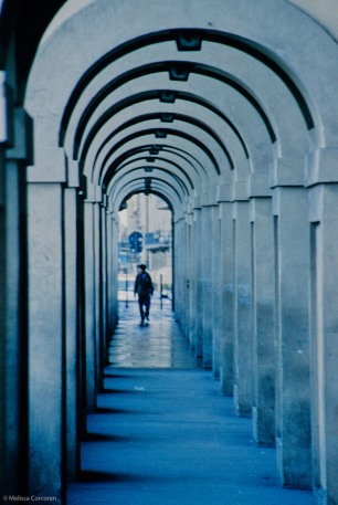 Early morning pedestrian in a covered sidewalk near the Arno River.