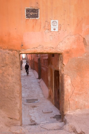Man riding a bicycle down an alleyway in Marrakech.