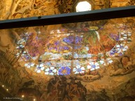 The reflection of one of the stained glass windows of the drum overlays the dome's fresco.