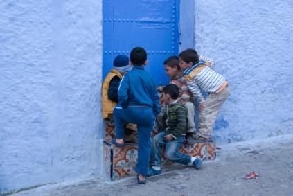 Boys play cards on a doorstep.