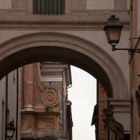An arch frames a circular architectural detail.