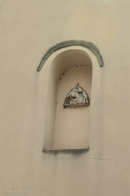 A wall shrine on a building by the side of the road.