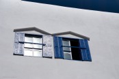 Two sets of blue shutters, one weathered to silver, against a background of white and blue.