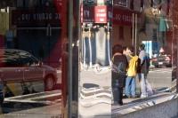 Street scene reflected in a building window.
