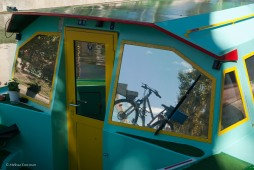 The windows of a boat reflect scenes from the canal tow path.