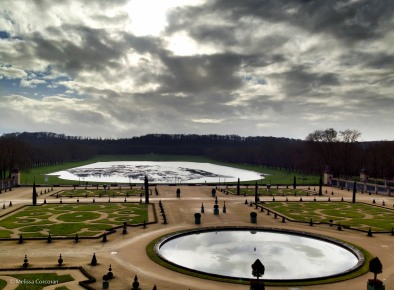 Ornamental pools reflect a cloudy sky.