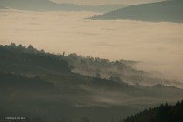 Fog washes down the hills and hides the valley.
