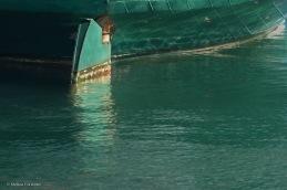 Green boat hull, rudder, and water.