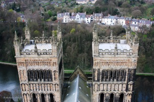 The view from the central tower of Durham Cathedral includes two other towers, the River Wear, and a residential neighborhood.