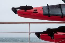 Red kayaks, gray sea and sky.